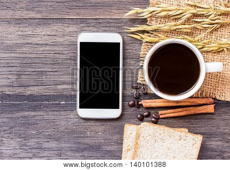 Ears of wheatsmart phone and coffee with slice of bread on a dark wooden table background.top view with copy space
