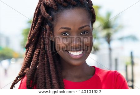 Amazing african woman with dreadlocks outdoor in city in summer