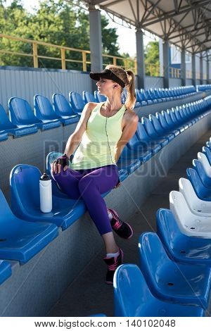 Sporty girl on the stadium. Stadium tribune. Slim sporty fitness woman. Bottle Shaker protein. Social media and fitness concept. Toned image.