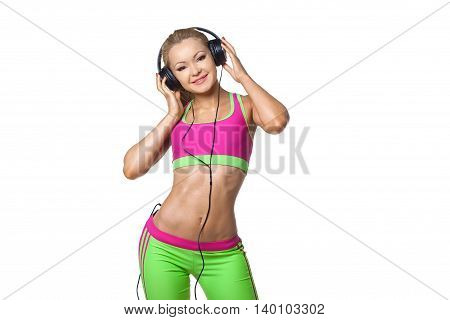 Happy sports woman listening music in big earphones isolated on a white background