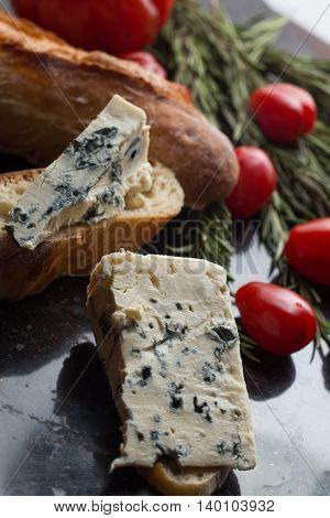 Blue Cheese With French Baguette, Tomato And Herbs On Black Marble Table. Traditional Snacks In Fran