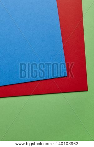 Colored cardboards background in green red blue tone. Copy space. Vertical
