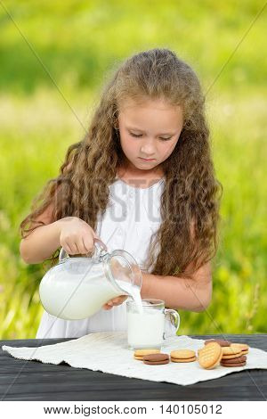 Little girl pouring milk in glass outdoor. Curly kid having breakfast. Summer time