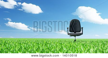 Office chair on a meadow with green grass and blue sky