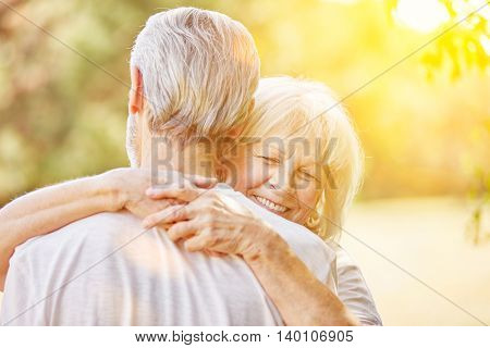 Happy woman and man hugging in summer in the nature
