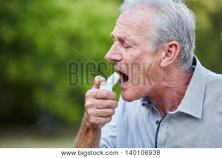 Old man using a spray as a medicine for hay fever in nature