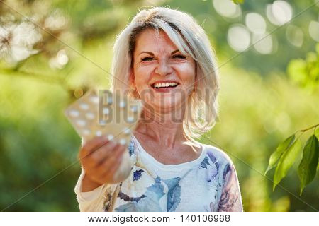 Senior woman with medicine laughs happily in the nature