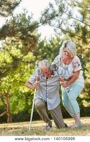 Woman helps man on crutches to stand up in the rehab