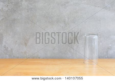 Water glass on the wood table in front of the cement wall background