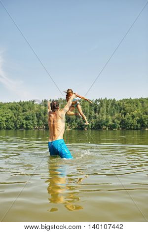 Father throws daughter in the water at the lake on the summer