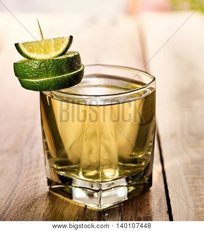 Healthy drink. On wooden boards is glass with green transparent drink. Drink number two hundred sixty-seven cold green tea with lime. Country life. Light background. Single lime glass.