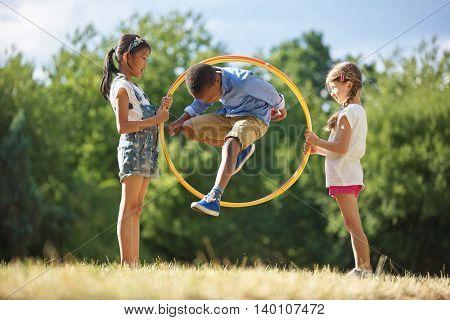 Boy jumps through hula hoop at the park