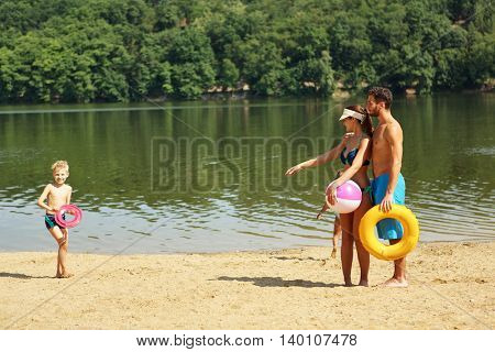 Family on the shore playing with a ball and a floating tire