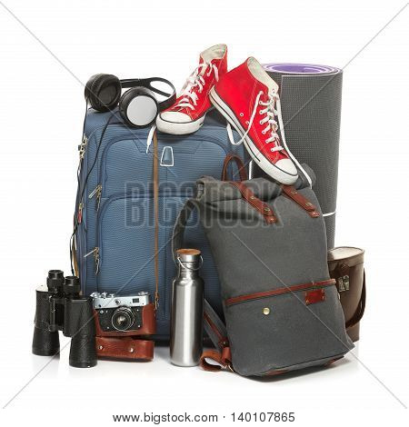 The suitcases, sneakers, retro camera, karrimat and binoculars on white background. The travel, tourism and holidays concept