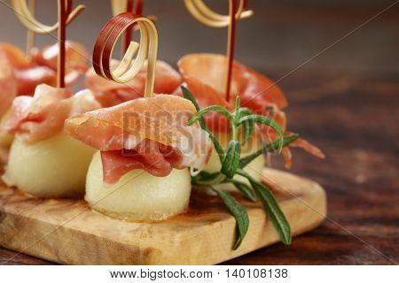 traditional Italian appetizer parma ham with melon - prosciutto melone