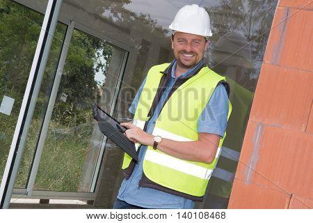 Unshaven Building Entrepreneur Using Digital Tablet On Site Under Construction