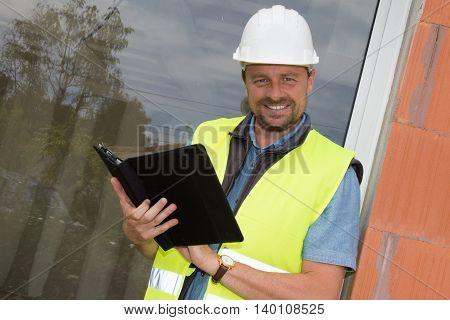 Building Entrepreneur Smiling Using Digital Tablet On Site Under Construction