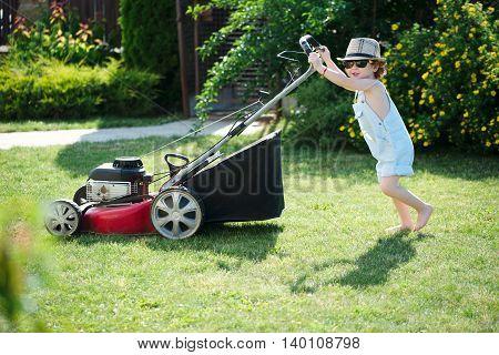 little cute boy mows lawn with mower