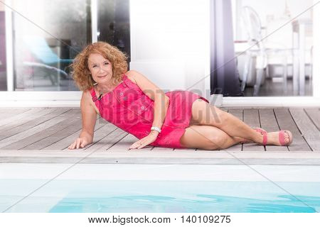 Smiling And Pretty Blond Middle Aged Woman Laying On Pool Deck