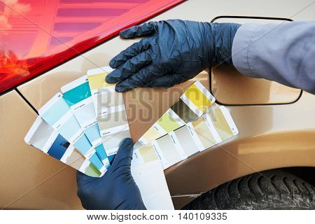 auto color matching. colorists man selecting color of car at automobile repair and renew service station with paint samples