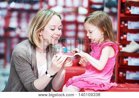 Family shoe shopping. Young woman mother with little child girl daughter choosing footwear