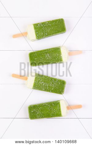 Frosty popsicles of kiwi in a row on a white wooden background