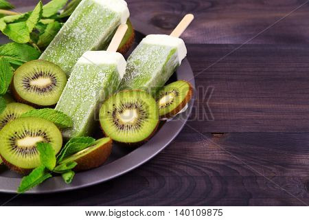 Homemade kiwi popsicles on a plate with mint and kiwi slices on a dark wooden background