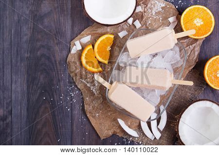 Homemade frosty orange and coconut popsicles on a plate with ice on a dark wooden background. Top view with copyspace