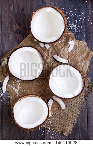 Fresh coconut halves with shell on a dark wooden table. Top view