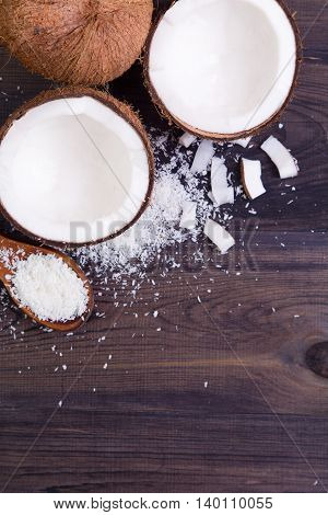Coconut halves with shell and shavings on a dark background. Top view with copyspace