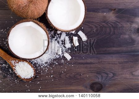 Coconut halves with shell on a dark background. Top view with copyspace