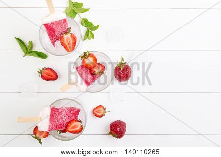 Homemade strawberry popsicles in a glass with mint on a white wooden background. Top view with copyspace