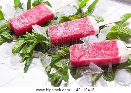 Homemade frosty strawberry popsicle on a mint with ice on a steel tray