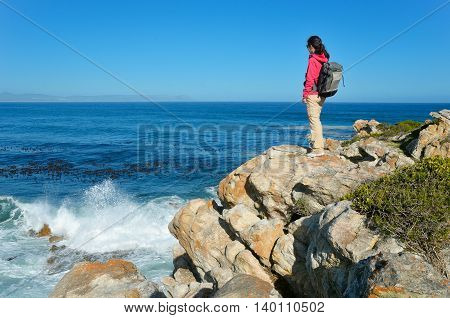 Woman looking at beautiful ocean view in Hermanus, vacation and travel in South Africa