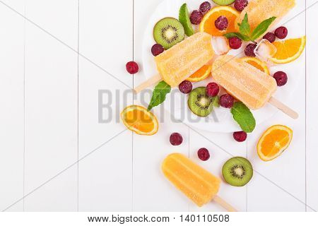 Homemade orange popsicles on a plate with mint kiwi frozen cherry and orange slices on a white wooden table. Top view with copyspace