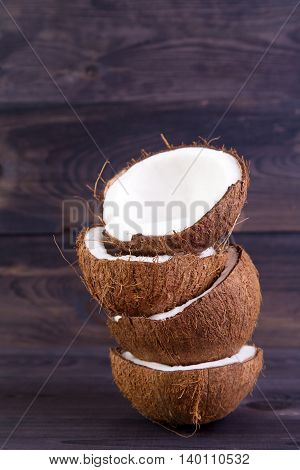 Tropical coconut halves with shell on a dark wooden table