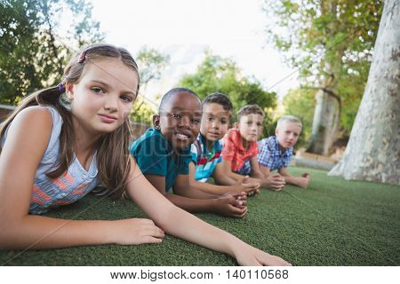Portrait of smiling schoolkids lying on grass in campus at school