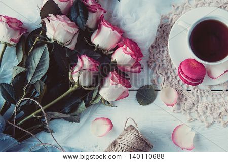 A Beautiful Bouquet Of Roses, Tea Cup,with Macaroons On  Distressed White Wood Table. Vintage Style
