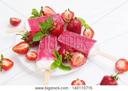 Homemade popsicles of strawberry on a plate with mint on a white wooden background
