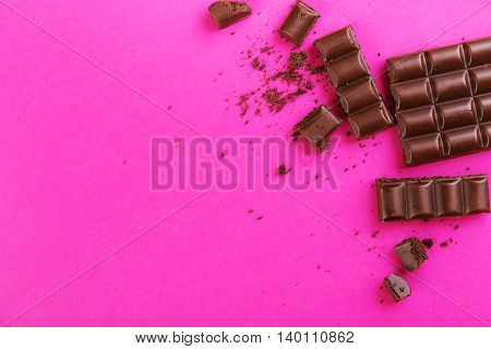 Broken dark chocolate bar with crumbs on a pink background
