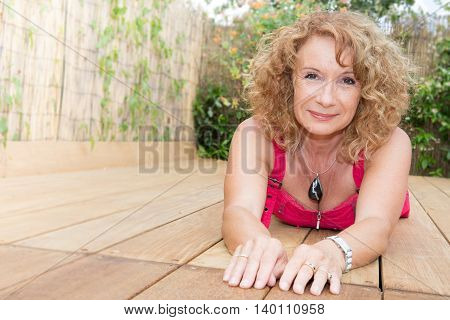 Gorgeous Blond Middle Aged Woman Laying On Pool Deck
