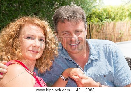 Picture Of Middle Aged Couple Sitting Outside The House