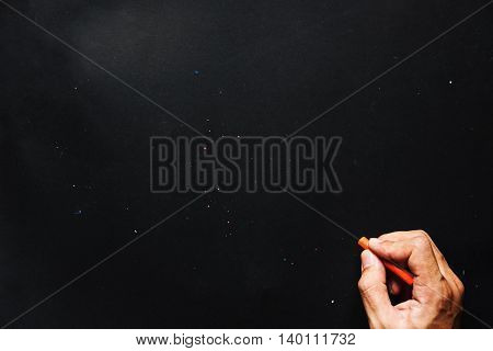 Hand hold orange crayon color, drawing on blackboard or black paper, and copy space