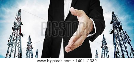Businessman extending hand with Telecommunication towers with TV antennas and satellite dish on blue sky