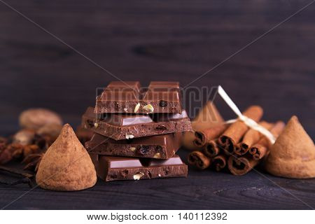 Broken chocolate bar with cinnamon anise and truffles on a dark wooden background. Space for text