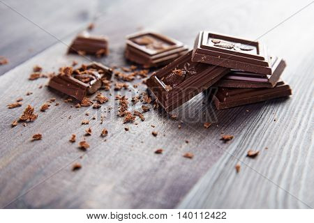 Broken dark chocolate bar with crumbs on a dark wooden background. Space for text