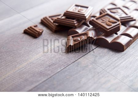 Broken dark chocolate bar on a dark wooden background. Space for text