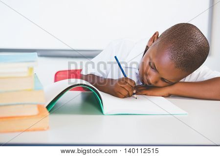 Schoolkid doing homework in classroom at school