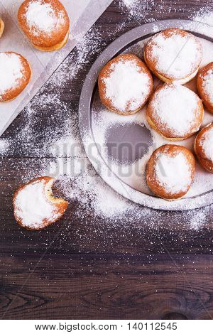 German donuts - berliner with jam and icing sugar in a tray on a dark wooden background. Top view with copyspace