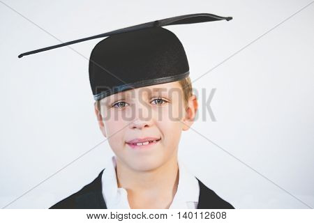 Portrait of schoolkid pretending to be graduate in classroom at school